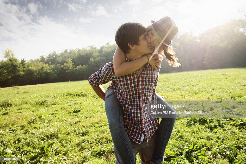 Man carrying girlfriend in rural field : Stock Photo