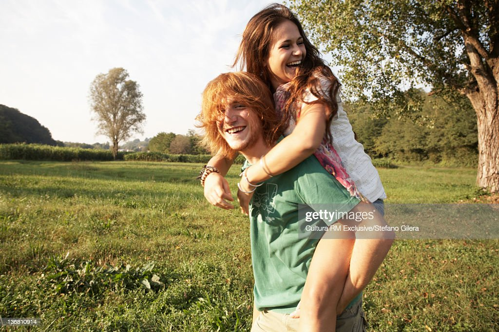 Man carrying girlfriend in rural field : Stock Photo