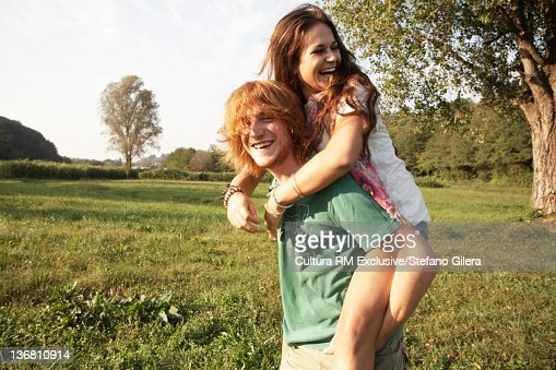 Man carrying girlfriend in rural field : ストックフォト