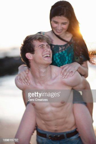 Man carrying girlfriend on beach : Stock Photo