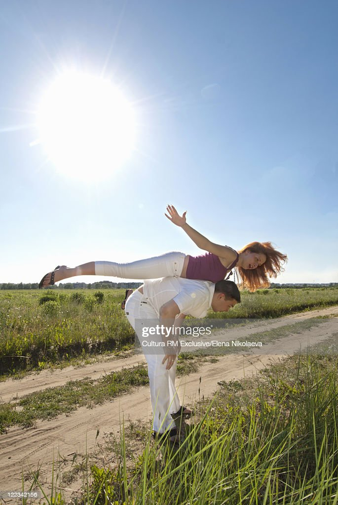 Man carrying girlfriend on rural road : Stock Photo