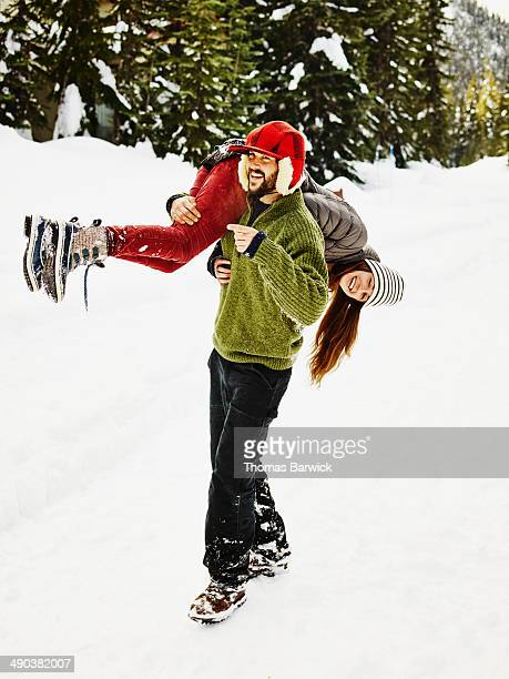 Man carrying girlfriend over shoulder in snow