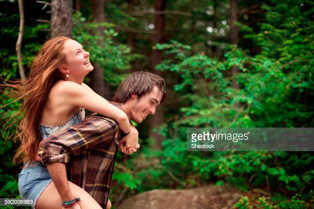 Man carrying girlfriend piggyback in forest