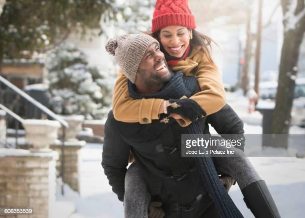 Man carrying girlfriend piggyback in snow