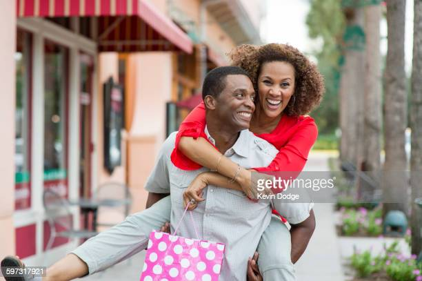 Man carrying girlfriend piggyback outdoors