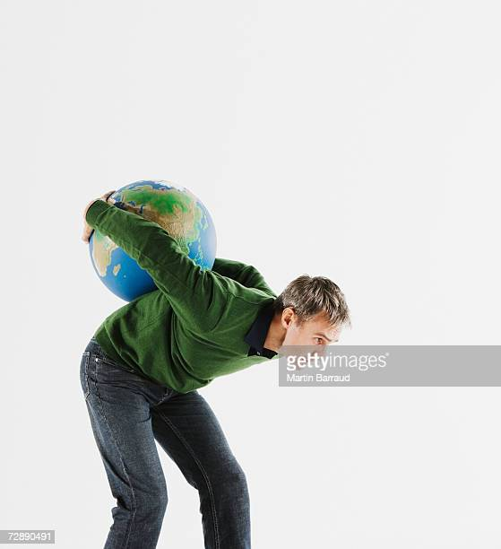 Man carrying globe on back against white background