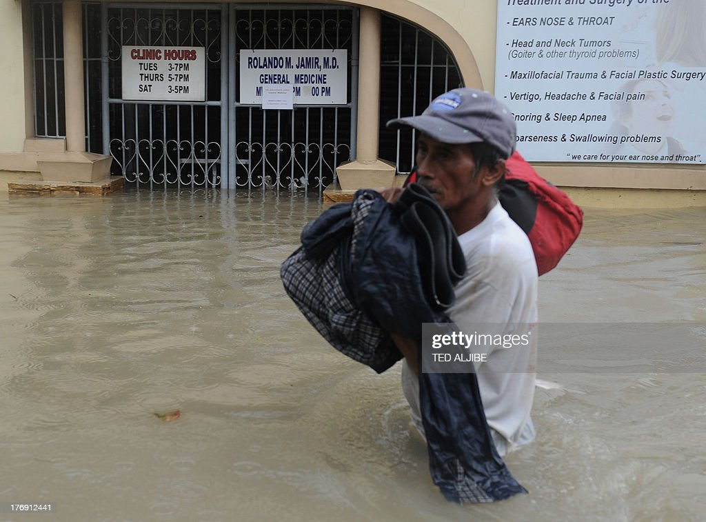 A man carrying his belongings wades through a flooded street in Cavite, southwest of Manila on August 19, 2013. Torrential rain paralysed large parts of the Philippine capital August 19, as neck-deep water swept through homes, while floods in northern farming areas claimed at least one life.