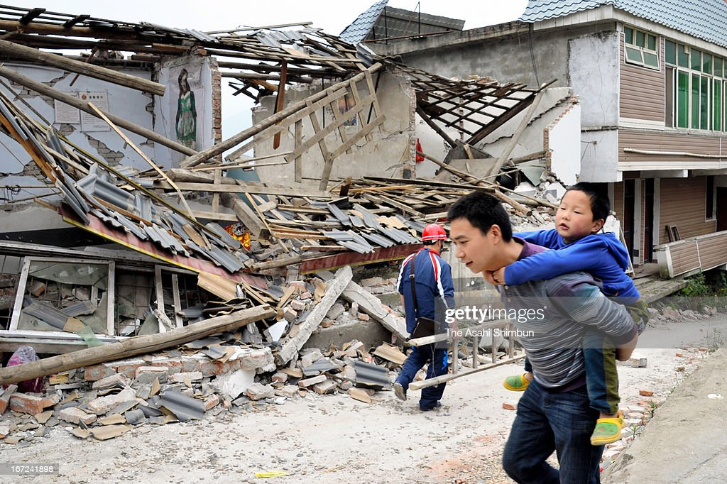 A man carrying his son on his back walks at destroyed city on April 22, 2013 in Luchan of Ya'an, China. A magnitude 7 earthquake hit China's Sichuan province on April 20 claiming over 160 lives and injuring thousands.
