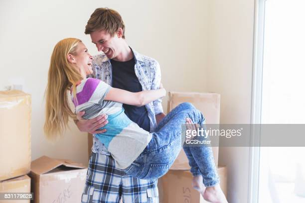 Man carrying his wife like a princess into their new home