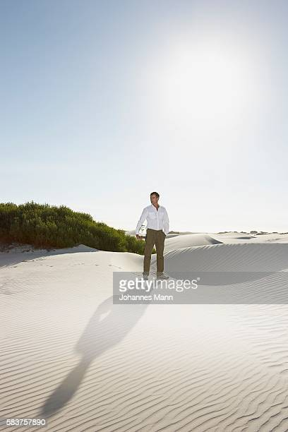 Man Carrying Jar with Plant in Desert