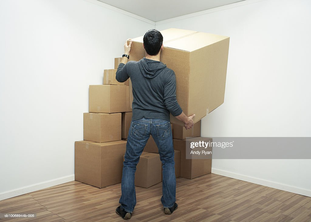 Man carrying large box in home, rear view