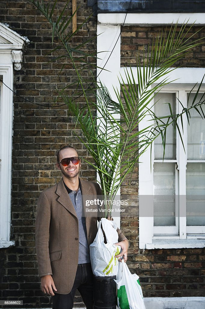 Man carrying large plant and shoppingbag. : Stock Photo