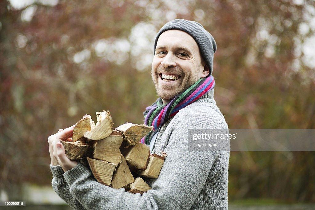 Man carrying logs : Stock Photo