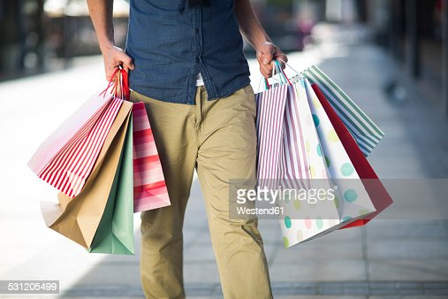 Man Carrying Lots Of Shopping Bags Stock Photo | Getty Images