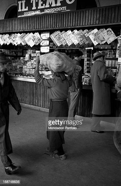 A man carrying on his head a heavy jute bag in a railway station In the background a bookstall with some hanging women's magazines Sicily March 1958