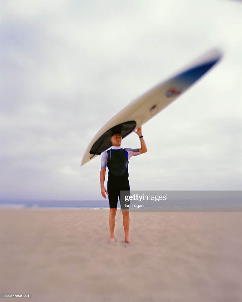 Man carrying paddleboard on head on beach (zoom effect) : Stock Photo