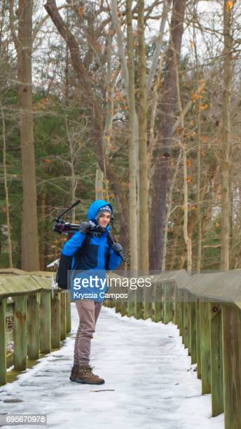 Man Carrying Photographic Equipment on Footpath