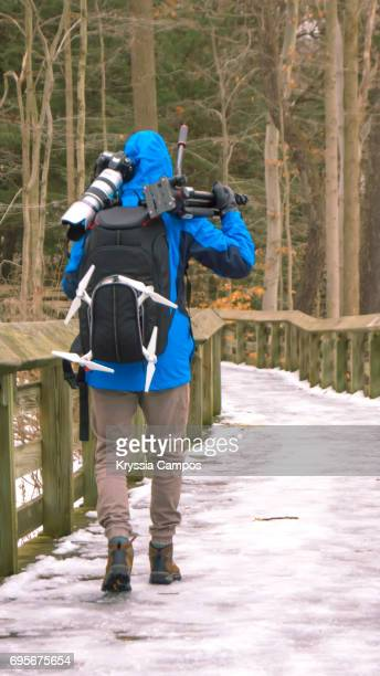 Man Carrying Photographic Equipment on Snow
