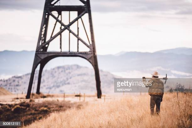 Man carrying pickaxe looks at large metal structure in field