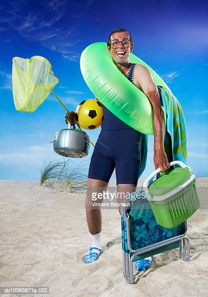 Man carrying picnic objects on beach