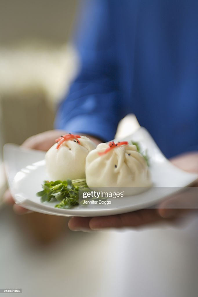 Man carrying plate of dim sum : Stock Photo
