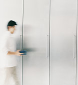 Man Carrying Plates past Cupboards, Blurred Motion