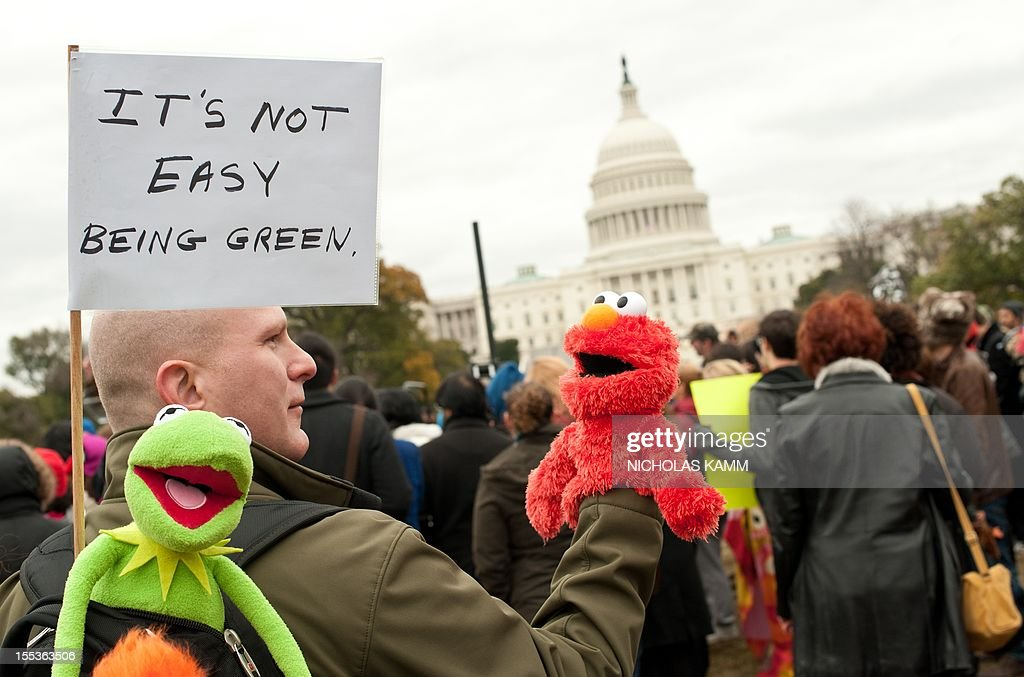 A man carrying puppets of Sesame Street characters Elmo and Kermit holds a sign in front of the Capitol during the 'Million Puppet March' in support of public broadcasting in Washington on November 3, 2012. Several hundred supporters of US public broadcasting in a good-humored protest prompted by US Republican candidate Mitt Romney's threat, in a televised debate with President Barack Obama a month ago, to halt government funding to public media if he wins the White House on ovember 6. AFP PHOTO/Nicholas KAMM