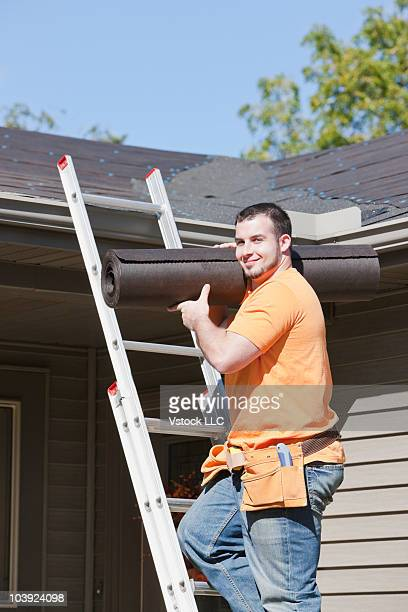 Man carrying roofing material while climbing up ladder