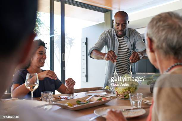 Man carrying salad to the table at family lunch