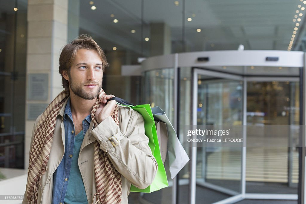Man carrying shopping bags on his shoulders