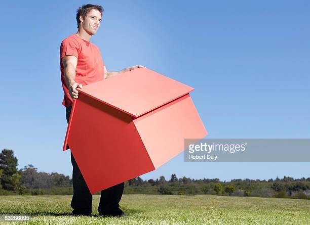Homme porter petite maison témoin dans le champ