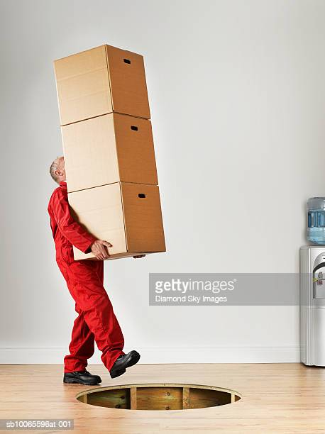 Man carrying stack of boxes, falling in hole of wooden floor