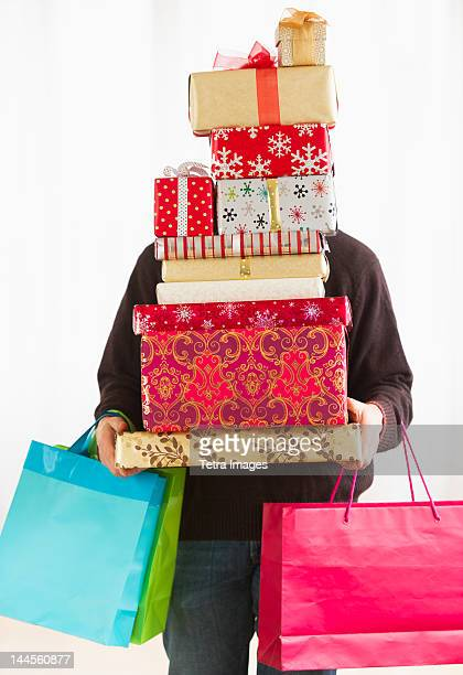 Man carrying stack of Christmas presents, studio shot