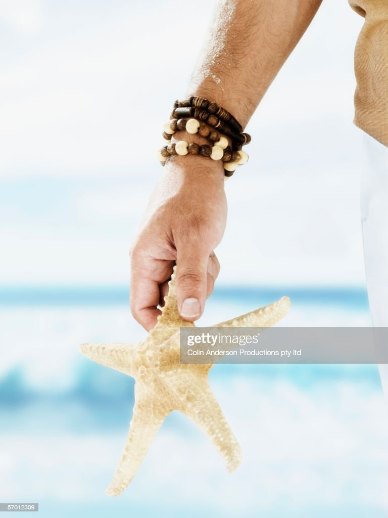 Man carrying starfish on the beach