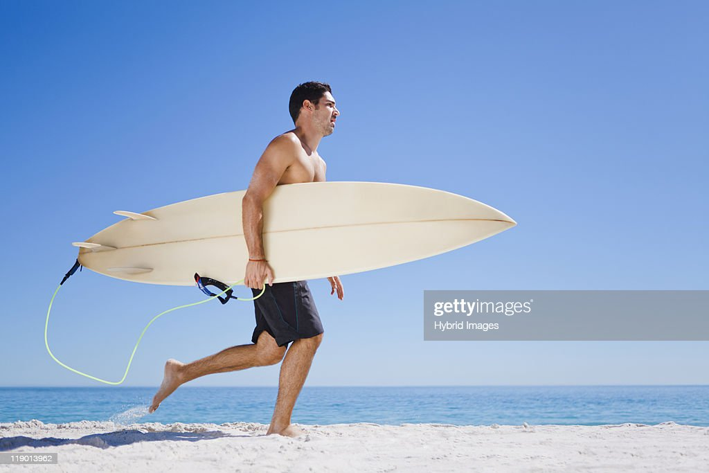 Man carrying surfboard on beach : Stock Photo