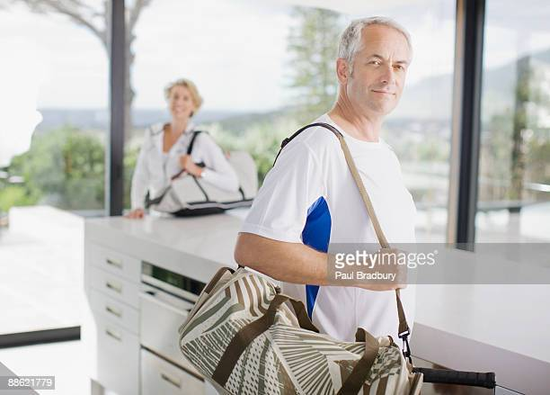 Man carrying tennis racquet in gym bag