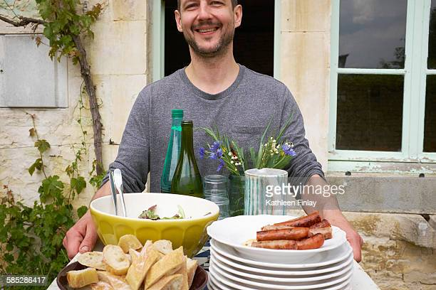 Man carrying tray of food outside house