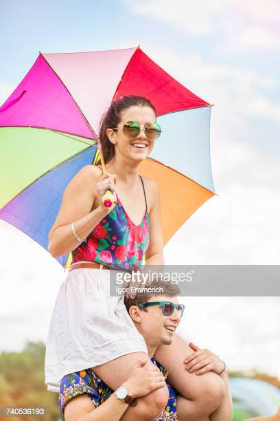 Man carrying woman holding umbrella on shoulders
