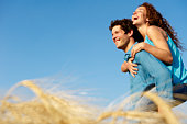 Man carrying woman in a wheat field