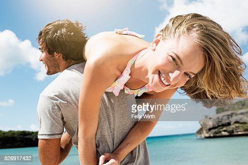 Man carrying woman on beach : Stock Photo