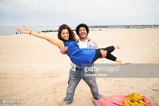 Man carrying woman on beach