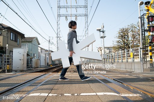 A man carrying Yen shape object and crossing