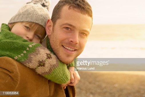 Man carrying young boy on beach. Autumn : Stock Photo