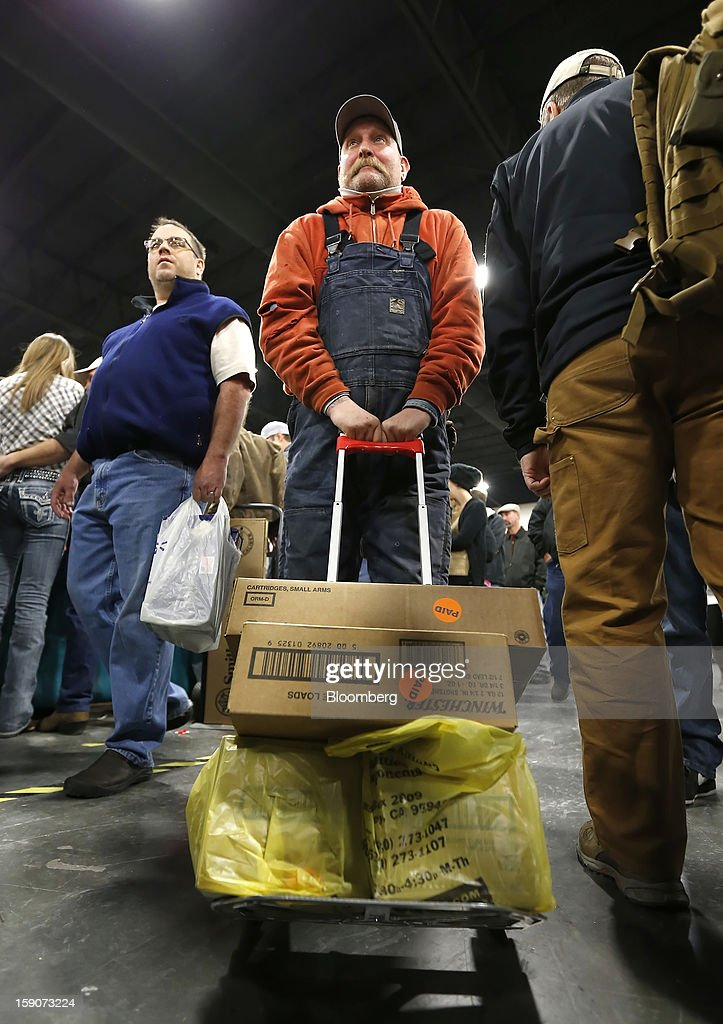 A man carts off several cases of ammunition purchased at the Rocky Mountain Gun Show in Sandy, Utah, U.S., on Saturday, Jan. 5, 2013. A working group led by Vice President Joe Biden is seriously considering measures that would require universal background checks for firearm buyers, track the movement and sale of weapons through a national database, strengthen mental health checks and stiffen penalties for carrying guns near schools or giving them to minors. Photographer: George Frey/Bloomberg via Getty Images