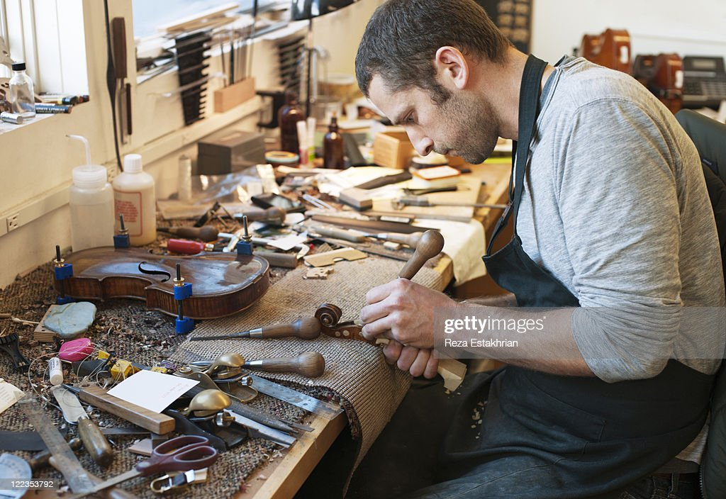 Man carves fiddle head : Stock Photo
