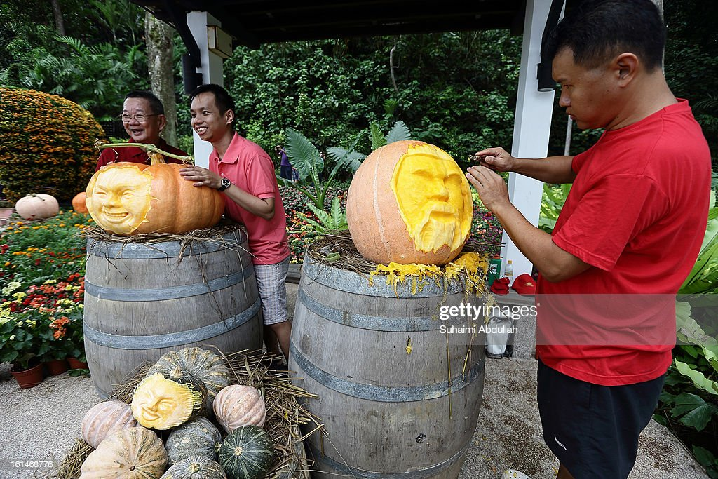 A man carves out a face from a pumpkin while visitors pose for photograph at the Sentosa Flowers exhibition at Palawan Beach on February 11, 2013 in Singapore. Millions of spring flowers decorate the island in celebration of the Chinese New Year, the year of the Snake.