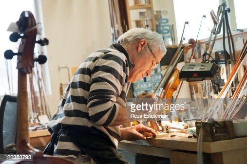 Man carves part for musical instrument : Stock Photo