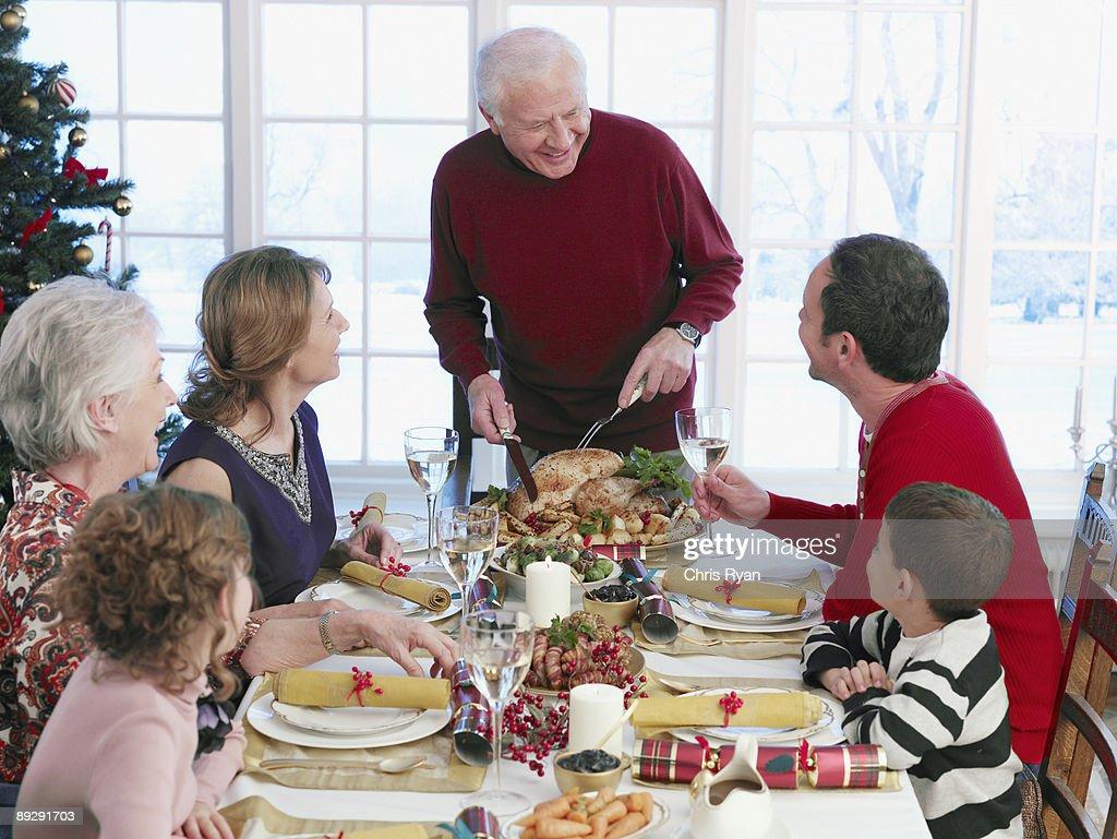 Man carving Christmas turkey at table : Foto stock