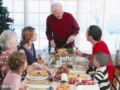 Man carving Christmas turkey at table : Stock Photo