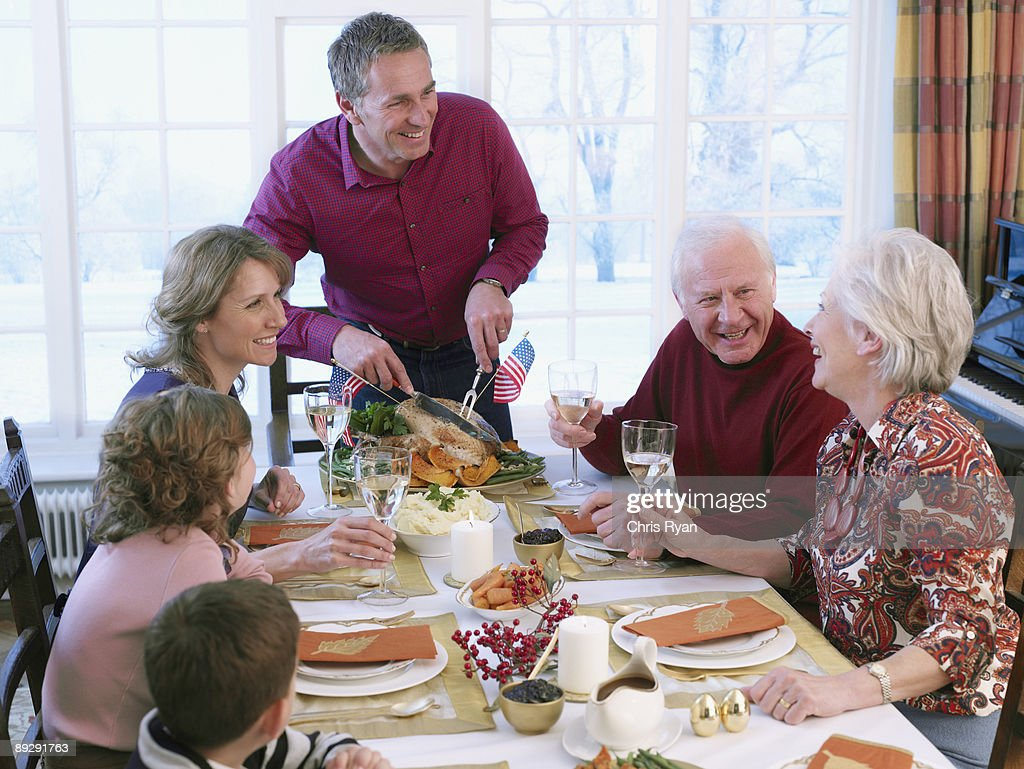 Man carving turkey for multi-generation family at table : Stock Photo